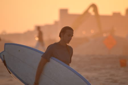 Nominated-Young surfer walking back in the beach after a great day in the surf with the sunset behind her
