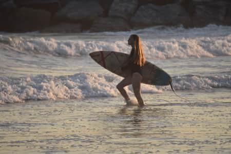 Young female surfer walking with h surfboard through the waves during golden hour