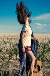Hippie girl in dress with guitar on the field