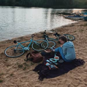 girl at an evening picnic on a sandy beach on a lake
