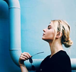 Blonde girl on a background of blue wall