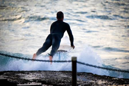 A surfer wearing a wetsuit launches headlong into the water on his surfboard. Enjoying life and feeling free