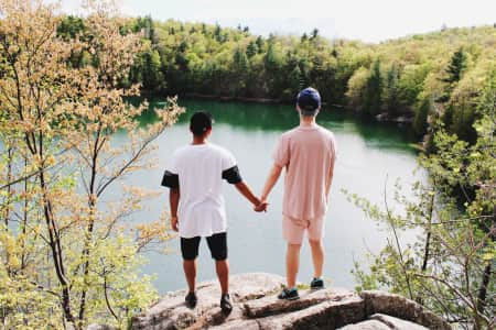 stand strong together! - lgbt - gay couple holding hands on the edge of cliff