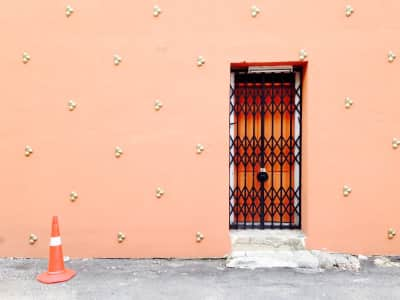 accordion door in peach colored wall with a traffic cone in view