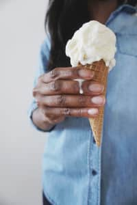 Hand holding slightly melting Ice Cream Cone