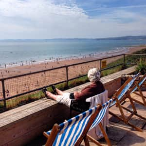 Senior, lady, older person, pensioner, sitting in the sun in a deckchair on a terrace overlooking a beach, resting, relaxing, watching, tourist, holiday, sunbathing, solitary, solitude