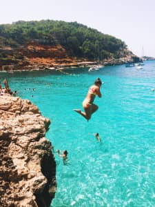 Girl cliff jumping into ocean