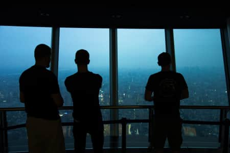 3 figures observing the city above as night falls