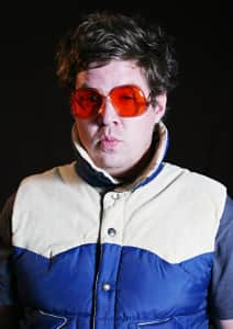 man in puffy vest and red tinted glasses puckers for the camera