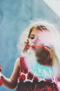 A young girl blowing bubbles in a summer dress