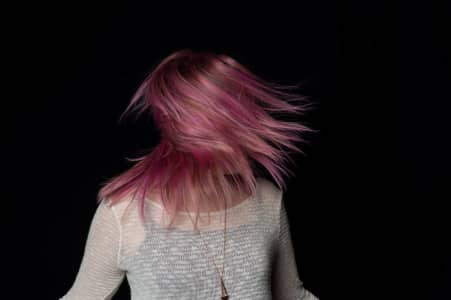 Young woman swinging her pink hair.