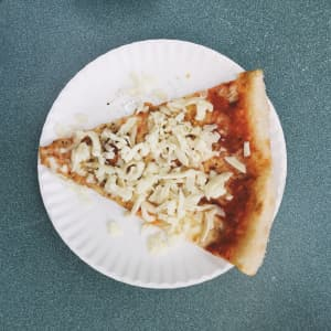 Pizza with extra cheese on a paper plate.