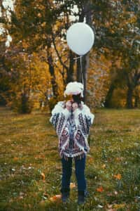 girl in autumn Park with a balloon and leaves