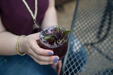 Woman's hand holding dark purple cocktail.