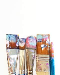 Group of five paintbrushes with wet paint on a white background.
