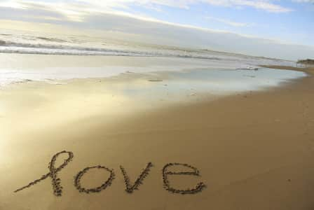 The word love is written in the sand, on the beach.