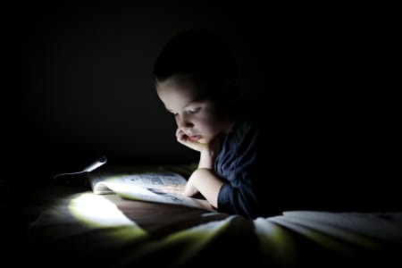 boy reading books in bed by book light in a dark room