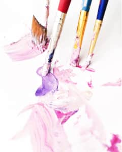 Four dirty colorful paintbrushes making abstract marks on a white background.