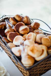 Rolls sit outside in a basket at a summer, outdoor, backyard wedding