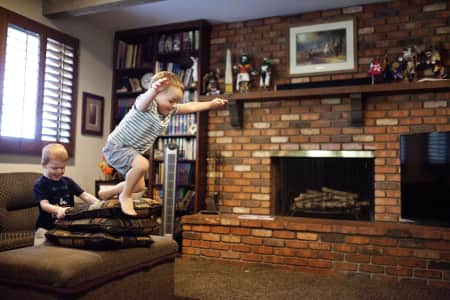 boy jumping off of pillows in a family living room