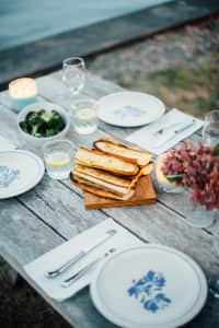 Garlic bread sits on a rustic table at a picnic by the water