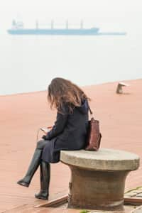 Young Woman Sitting Alone At The Dock Using Her Smartphone And Listening Music