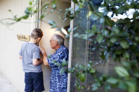 grandpa and grandson working together to fix and repair a sliding door at home