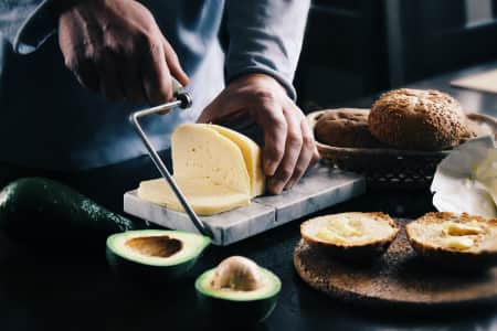 The man prepares sandwiches from grain bread, oil, cheese and avocado