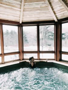 Woman enjoying an indoor hot tub at a snowy spa.