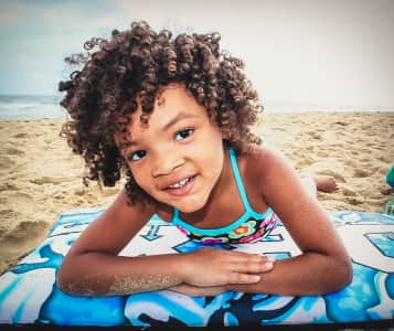 Little girl wth curly hair at the beach