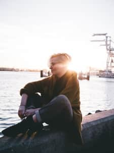 Girl at sunset sitting in marina