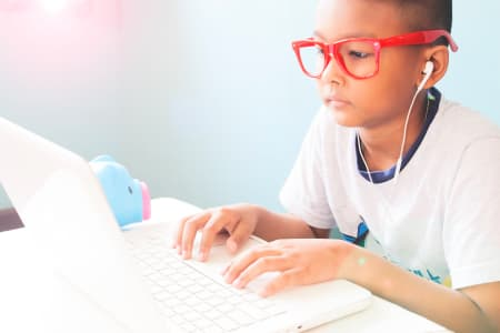 Little boy listening and using laptop computer