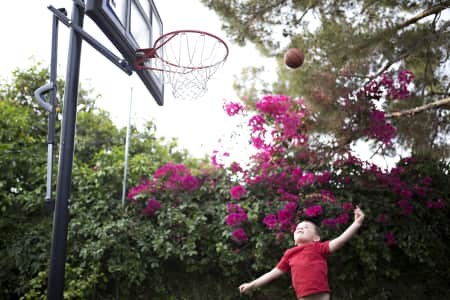 Boy shooting basketball on trampoline