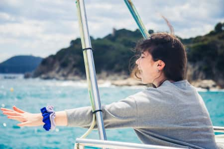 A young girl emotionally expresses her happiness, rejoicing at sea travel.