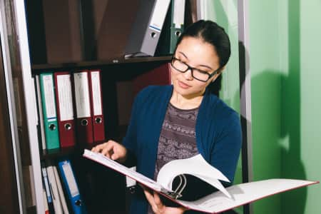 Young asian business woman browsing the folder with documents near the locker