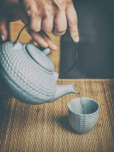 woman serving hot tea in a traditional kettle and cups.