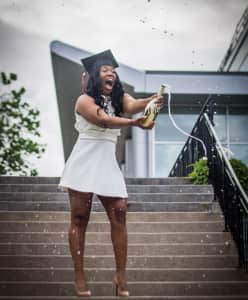 Girl popping champagne bottle after graduation.