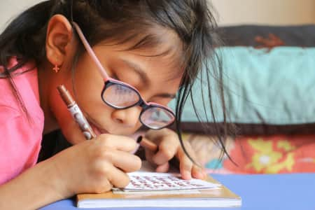 Little girl writing on a notepad.