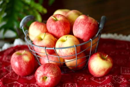 Gala apples in a wire basket on a red bandana-print tablecloth