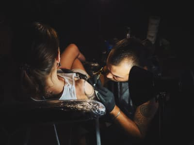 Tattoo artist making ink tattoo to young woman in studio