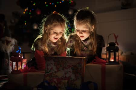Christmas night. Two girls open the gifts under the tree. New year's stories. Real emotions