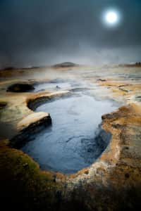 Hverir, iceland. Hot mud acid pool with dramatic landscape with full moon in the fog