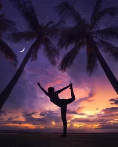 Yoga silhouette at the park between palm trees with amazing sunset