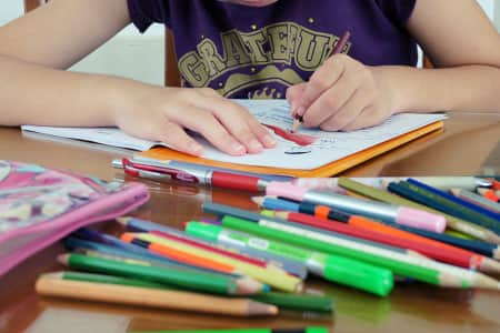 Student holding colors pencils on wooden table with coloring work closeup