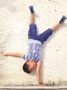 Upside down! Optical illusion of a boy doing a hand stand on a wall. Flat lay.