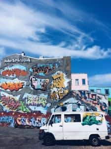 Street art, walls and car, bright daylight and colors, blue sky, city life, urban architecture, white clouds, colorful, graffiti, copy space