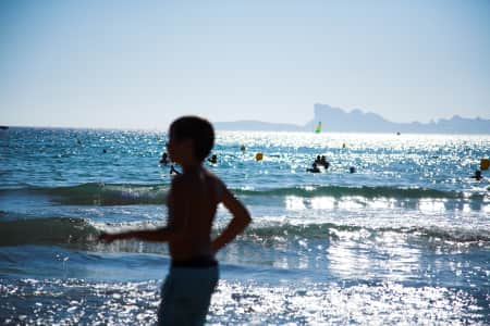 Young kid silhouette at the beach, bright sunlight, blue sea and waves, recreation and leisure, summertime, clear blue sky, family vacations, sunny day, background, copy space