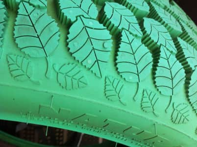 Revolutionary ecological green tire : the future is on the way, closeup, leaves shapes, patterns, natural light, inventive, creative, futuristic, responsibility, background, copy space