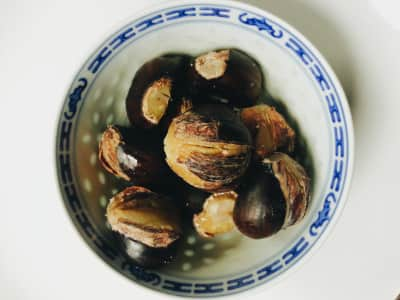 bowl of home made cooked fresh chestnuts, blue and white porcelain cup, dessert, closeup, from above, flat lay, natural light, copy space