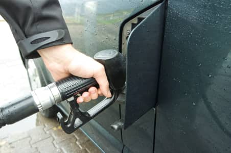 Hand of a man holding fuel pump and refueling his green van on the rainy day.